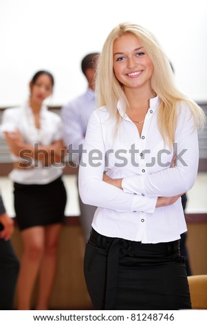Portrait of young happy caucasian woman with her colleagues at the background