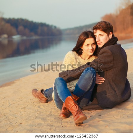 Portrait of young happy couple. Young handsome man embracing young beautiful brunette outdoor in the park.