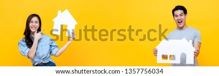 Portrait of young happy excited Asian man and woman holding paper homes on yellow banner background for real estate concept