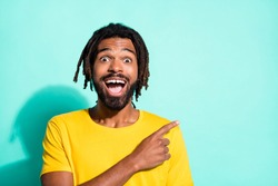Portrait of young happy excited crazy smiling african man pointing finger in copyspace isolated on turquoise color background