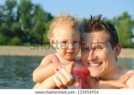 Portrait of young happy father with little curly haired daughter