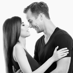 Portrait of young happy hugging couple, standing close and looking at each other, with smile. Love, relationship, dating, flirting, lovers, romantic concept. Black and white.