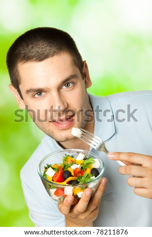 Portrait of young happy man eating salad, outdoors