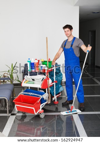 Portrait Of Young Happy Man Standing With Cleaning Equipment In Office