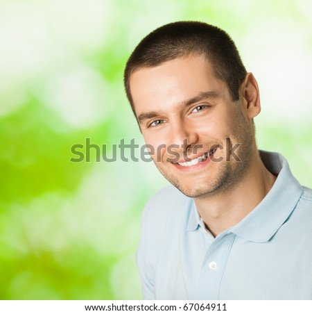 Portrait of young happy smiling attractive man, outdoors. You can use left part for slogan or text.