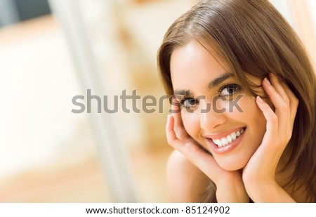 Portrait of young happy smiling beautiful woman, at home. You can use left part as copyspase for slogan or text.