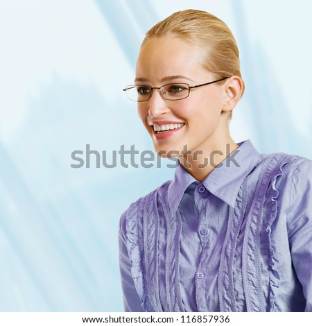 Portrait of young happy smiling blond business woman, at office