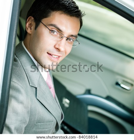 Portrait of young happy smiling businessman in the car