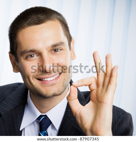 Portrait of young happy smiling successful gesturing business man with okay hand sign at office