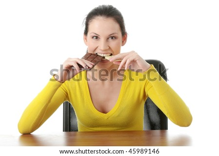 Portrait of young happy smiling woman eating dark and white chocolate