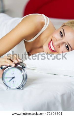 Portrait of young happy smiling woman waking up at bedroom