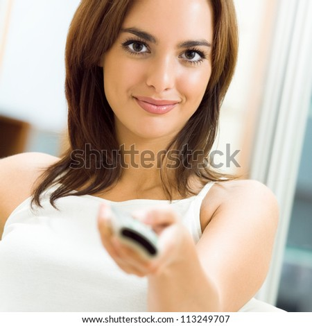 Portrait of young happy smiling woman watching TV at home