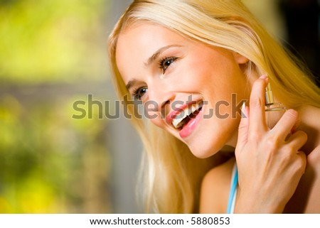 Portrait of young happy smiling woman with perfume bottle indoors