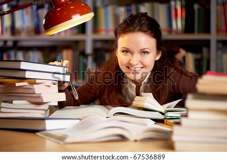 Portrait of young happy teacher sitting at the table and touching books