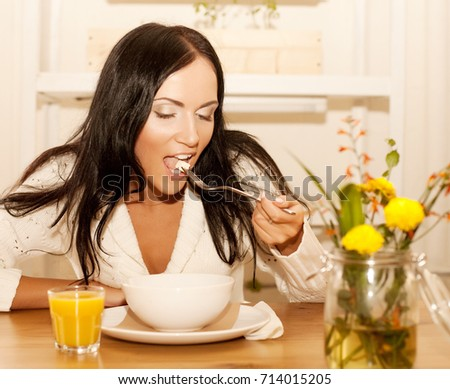 Portrait of young happy woman eating salad at home