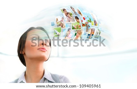 Portrait of young happy woman looking at photo and video files of her family in social media resources. Indoors at office