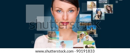 Portrait of young happy woman sharing his photo and video files in social media resources. Studio shot against blue background