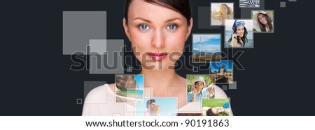 Portrait of young happy woman sharing his photo and video files in social media resources. Studio shot against gray background