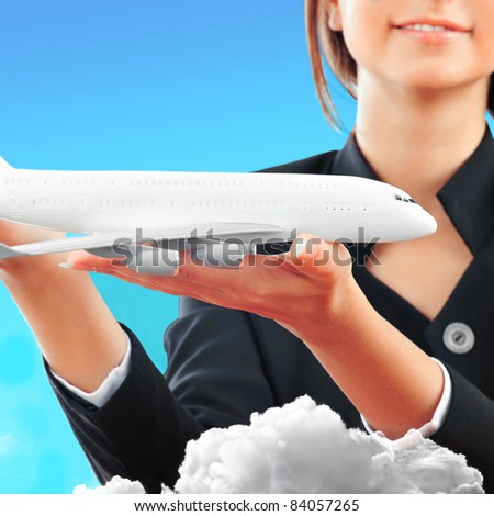 Portrait of young happy woman stewardess holding jet aircraft in her arms on foreground. Advertisement banner for transport companies