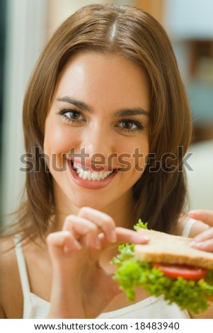 Portrait of young happy woman with sandwich at home