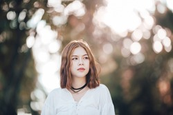 Portrait of young hipster Asian girl  posing in the autume park forest bokeh background