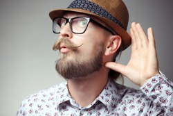Portrait of young hipster cupping hand behind ear - can't hear you concept