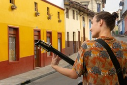 portrait of young hispanic man in the center of bogota, la candelaria in the middle of colorful colonial houses playing a guitar, he is a musician who plays in the street in an artistic performance