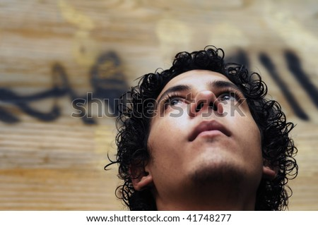 Portrait of young hispanic teen boy against grunge background