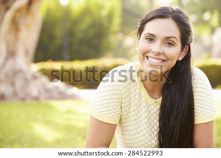 Portrait Of Young Hispanic Woman Sitting In Park #284522993