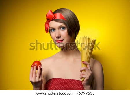 Portrait of young housewife holding tomato and pasta in her hands. Retro styled. Isolated on yellow background - stock photo