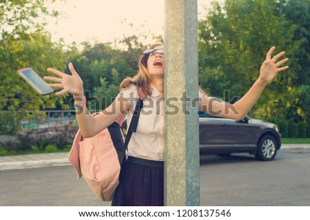 Portrait of young inattentive girl, distracted by mobile phone. Girl crashed into street post, dropped phone. Stockfoto ©