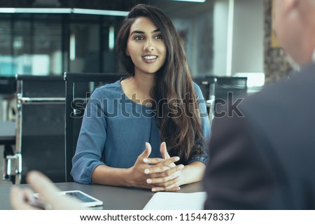 Portrait of young Indian female client or candidate sitting at table, talking to senior male manager and smiling in office. Job interview or consultancy concept #1154478337
