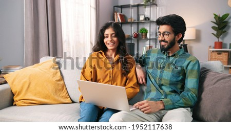 Portrait of young Indian happy cheerful family couple resting on sofa in living room searching internet typing online on laptop computer and speaking, choosing decor, e-commerce, leisure concept