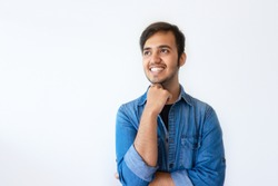 Portrait of young Indian man looking upwards and smiling. Positive handsome dark haired man wearing denim shirt propping up chin with right hand. Happy memory concept.