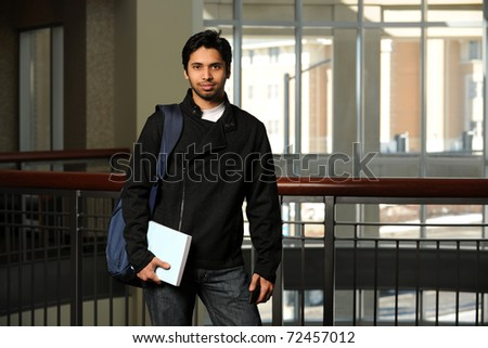 Portrait of young Indian student holding book inside building