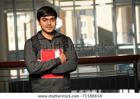 Portrait of young Indian student with school backpack holding notebook inside school building