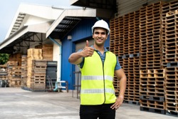 Portrait of young Indian worker working in logistic industry outdoor in front of factory warehouse. Smiling happy man with hard hat looking at camera giving thumbs up gesture at depot