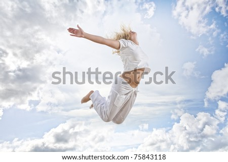 Portrait of young jumping woman on blue sky background