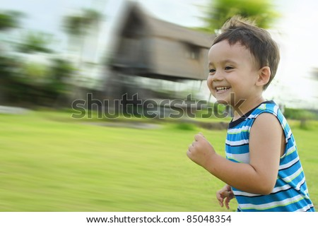 portrait of young kid running and smiling in the park