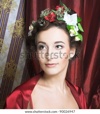 Portrait of young lady in red dress with flowers in her hair.