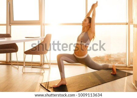Portrait of young  lady in sporty top standing and practicing yoga on yoga mat at home with big beautiful windows on background #1009113634
