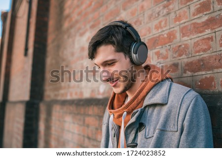 Portrait of young latin man listening to music with headphones against brick wall. Urban concept.