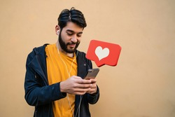 Portrait of young latin man using his mobile phone. Red heart like notification. Social media and communication concept.