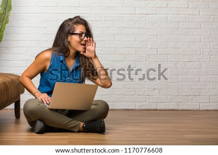 Portrait of young latin woman sitting on the floor whispering gossip undertone, trying not to be heard, is warning of a possible weakness or an opportunity. Holding a laptop.