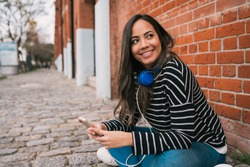Portrait of young latin woman with headphones and using her mobile phone in the street. Outdoors.