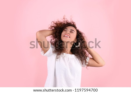 Portrait of young laughing African-American woman on color background #1197594700