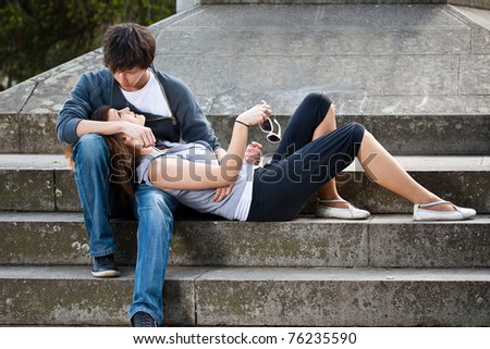 Portrait of young love couple sitting together on steps of a building
