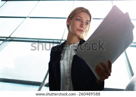 Portrait of young lovely business woman examining paperwork in light office interior sitting next to window, filtered image with flare sun light from the window