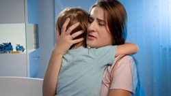 Portrait of young loving mother soothing and caressing scared little boy in children room at night. CHild being scared and crying of nightmare or bad dream.