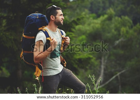 Shutterstock Portrait of young male backpacker with a rucksack standing on the mountain hill while enjoying nature scenery view with plants copy space area background for your text message or advertising content